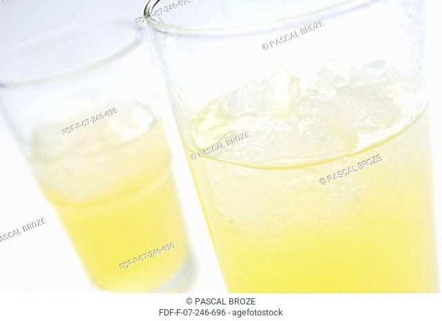 Close-up of two glasses of orange soda with ice cubes
