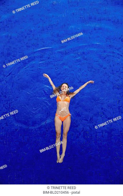 Caucasian woman floating in swimming pool