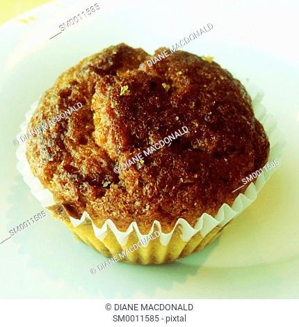 A healthy raisin bran muffin on a white plate