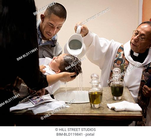 Priest baptizing boy in church