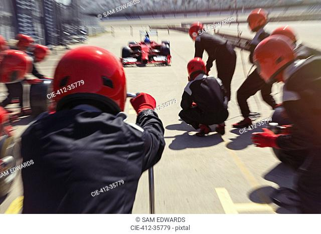 Pit crew ready for nearing formula one race car driver in pit lane