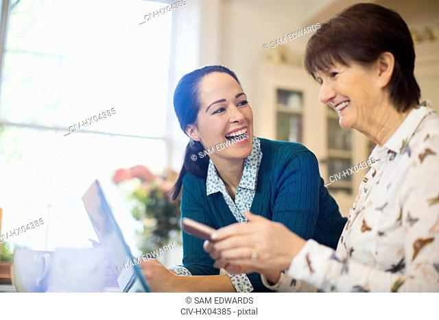 Happy daughter helping senior mother using laptop