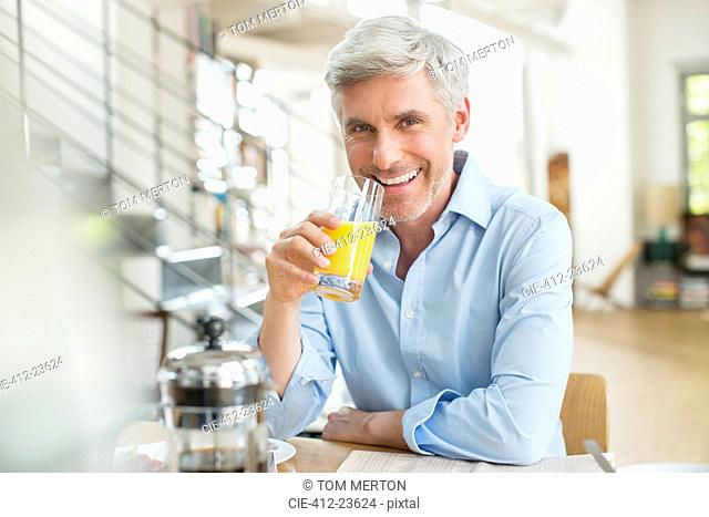 Older man drinking orange juice at breakfast table