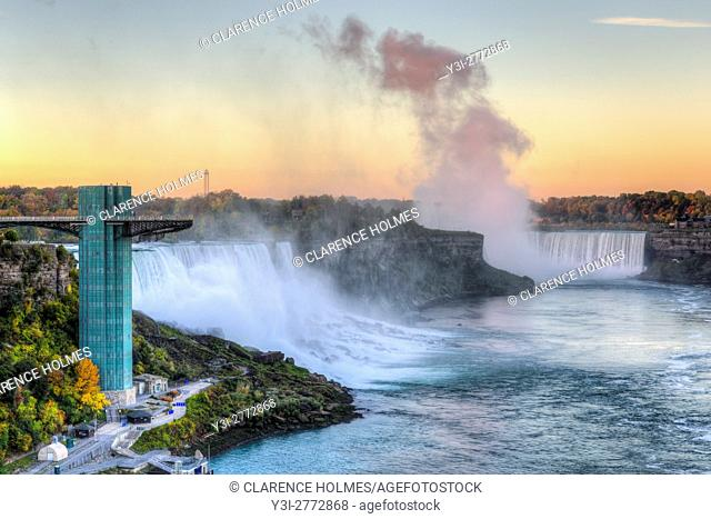 Soft light from the rising sun reflects off the spray from Horseshoe Falls with the American Falls on the left just after sunrise in Niagara Falls