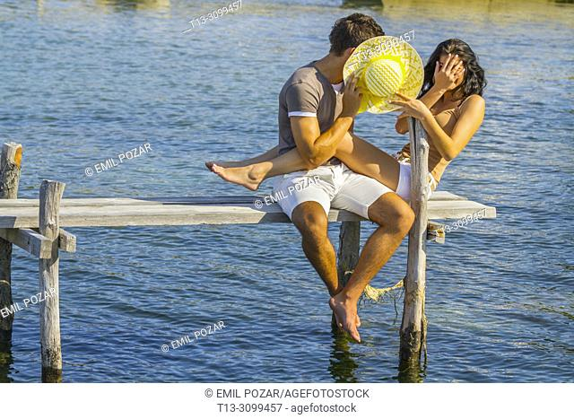 Young couple Summer vacation hiding behind Yellow hat