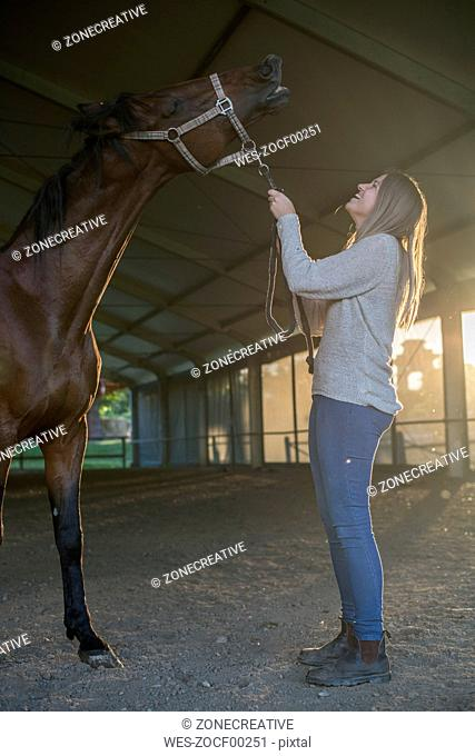 Happy young woman with horse in riding arena