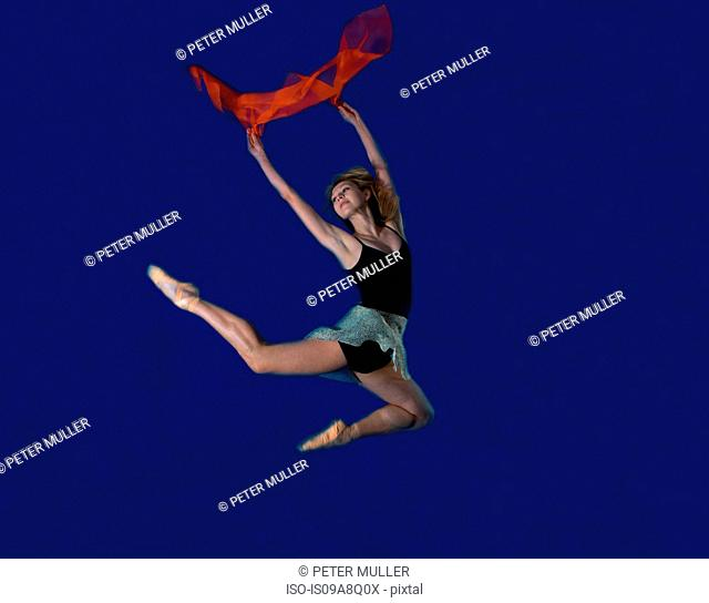 Young female dancer jumping mid air with red scarf