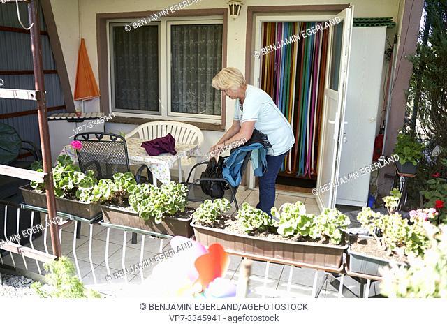 senior woman packing her bag on terrace of allotment garden house