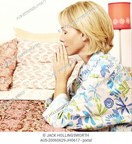 Side profile of a mature woman praying in a bedroom
