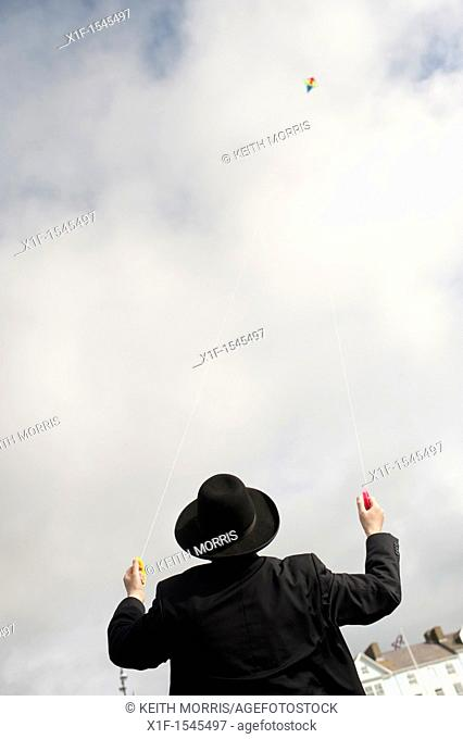 Flying a kite: Orthodox Hassidic jews on summer holiday on the beach at Aberystwyth Wales UK