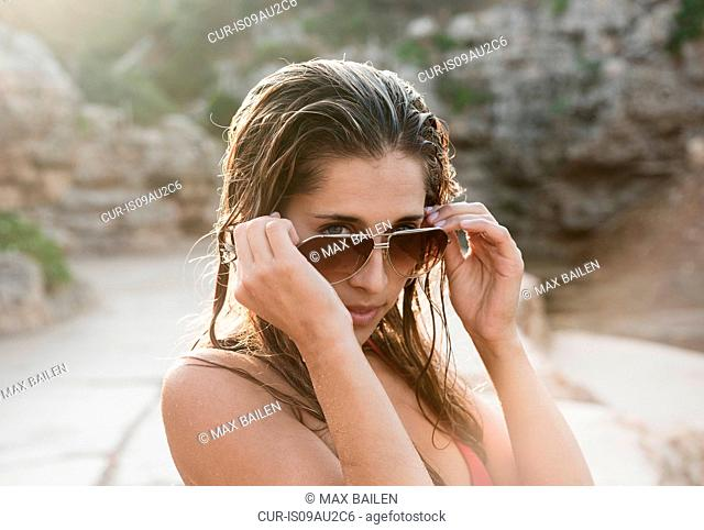 Portrait of young woman looking over her sunglasses