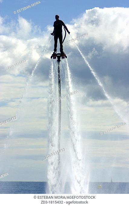 Man practicing flyboard new water sport in Barcelona, during Festa al cel Airshow 2012