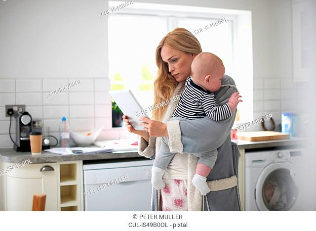 Mother standing in kitchen, holding baby boy, looking at digital tablet