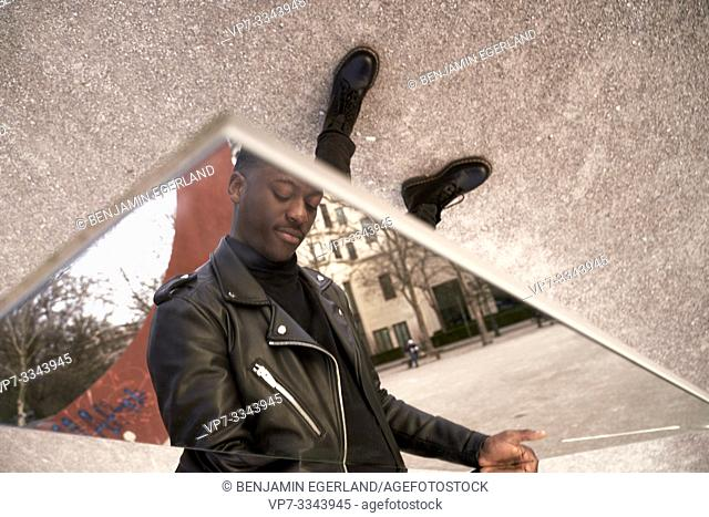 young African man looking down at his feet, in Munich, Germany