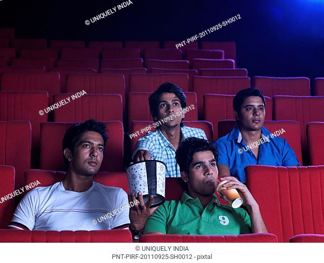 Youngsters enjoying movie with popcorns in a cinema hall