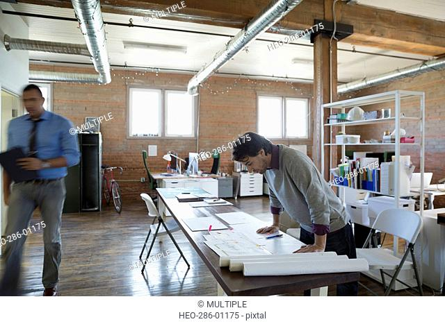 Designer reviewing plans in office