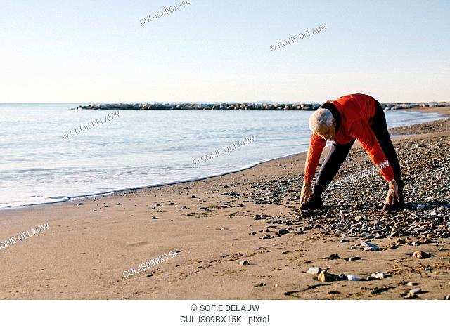 Senior man doing stretching exercises on beach, Livorno, Italy