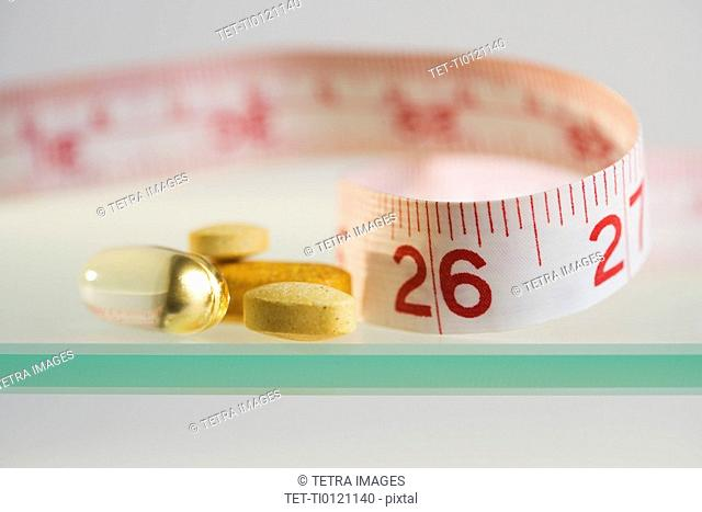 Close up of pills and measuring tape