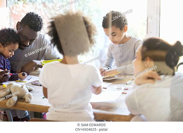Young family coloring at dining table