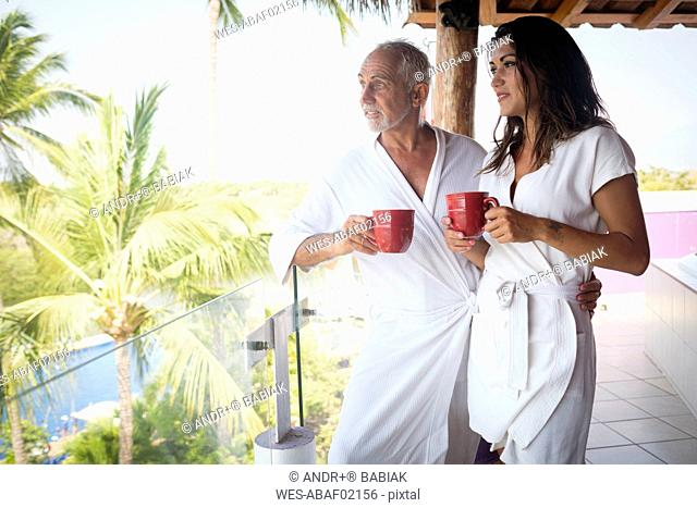 Young woman and older man drinking coffee in bathrobes on balcony