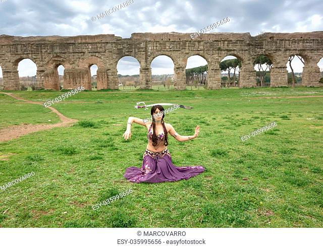 belly dancer with sword under the ancient Roman aqueduct