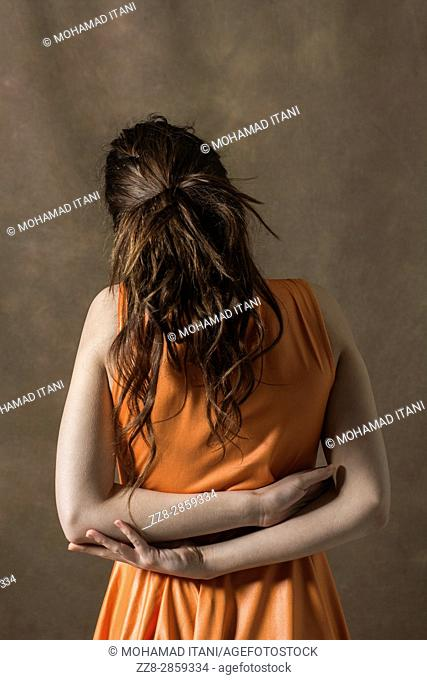 Rear view of a young woman hands behind her back