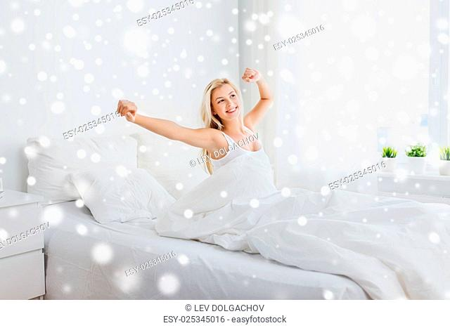 rest, sleeping, comfort and people concept - young woman stretching in bed at home bedroom over snow