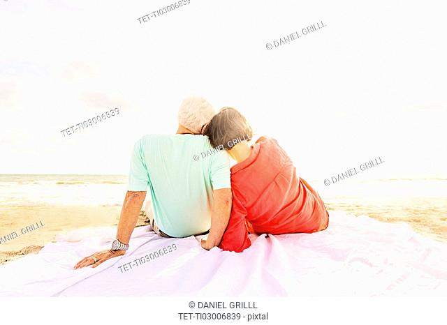 Rear view of couple sitting on beach at sunrise