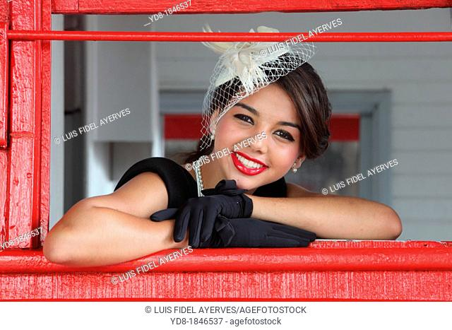 Young woman posing in the window and looking at the camera from one of the trains of the Gold Coast Railroad Museum, Miami, Florida, USA