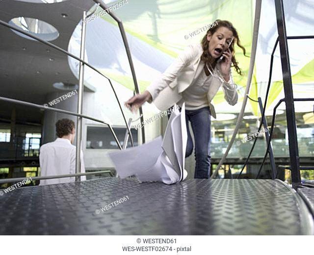 Young businesswoman using mobile phone, papers falling on floor