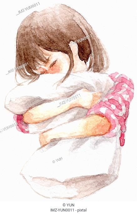 A young girl clutching a pillow