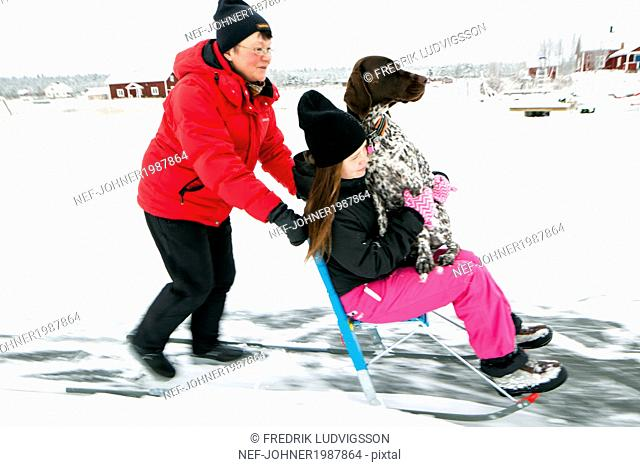 Mother pushing sledge with girl and dog