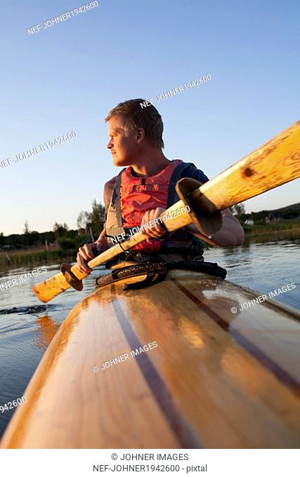 Young man kayaking, Sweden