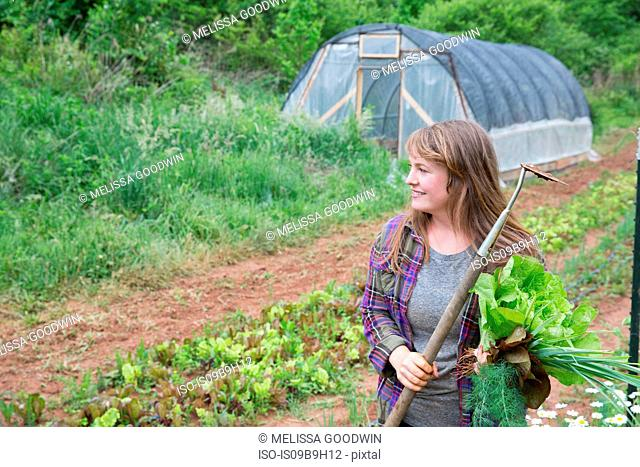 Woman with hoe in vegetable garden looking away smiling