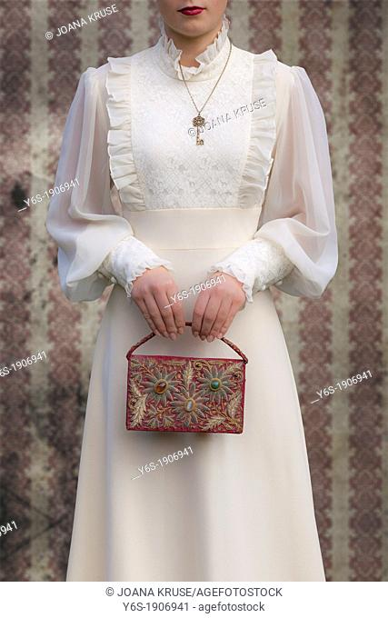 a woman in a victorian dress with a red, beaded handbag