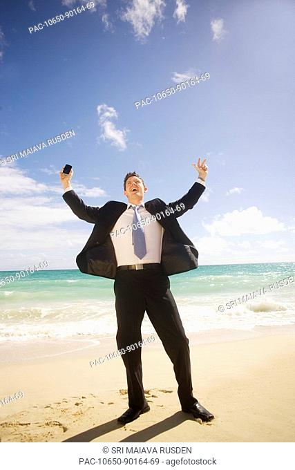 Hawaii, Oahu, young man at the beach in business attire