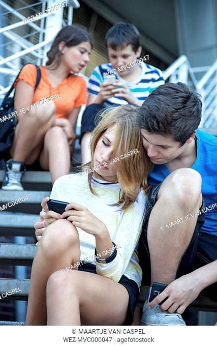 Teenage friends using mobile devices on stairs