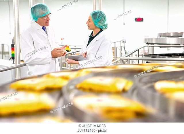 Quality control workers talking behind production line in cheese processing plant