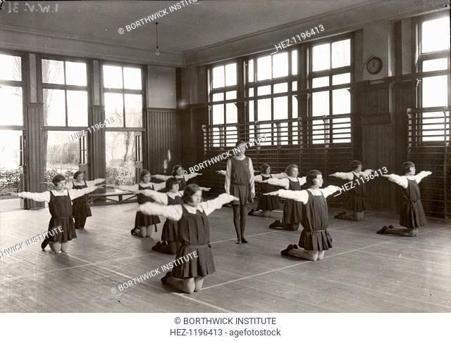 Rowntree girls in an indoor gymnastic class, 1930. The girls kneel on the floor with arms outstretched. Gym classes were part of the educational curriculum for...