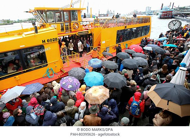 People carrying umbrellas wait on the pier in front of a harbor ferry that will take them to the theaters on the other side of the Elbe river in Hamburg