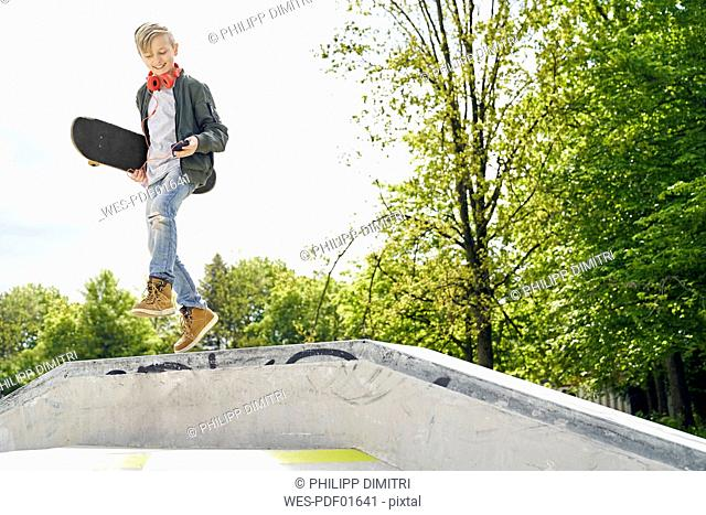 Boy with headphones and smartphone jumping off ramp in skatepark