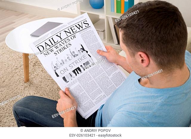 High angle view of mid adult man reading news on newspaper at home