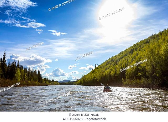 Woman packrafting down Beaver Creek, National Wild and Scenic Rivers System, White Mountains National Recreation Area, Interior Alaska; Alaska