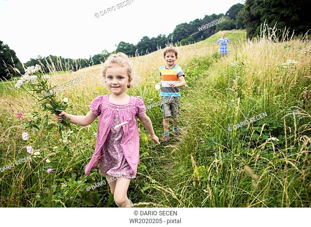 Mother with children picking flowers in the meadow
