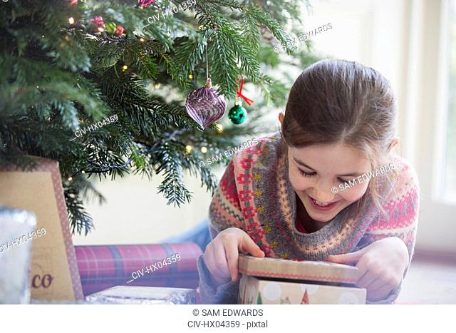 Smiling, curious girl opening Christmas gift