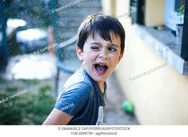 Boy soaked by water gun. Italy