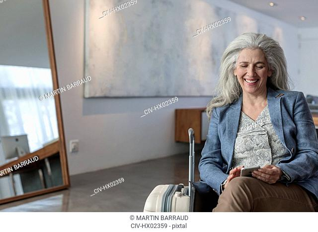 Smiling mature woman with suitcase texting with cell phone