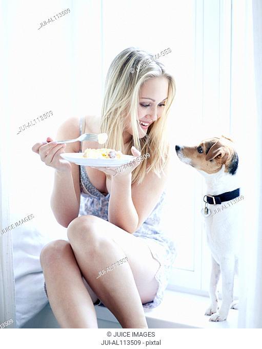 Teenage girl eating with pet dog