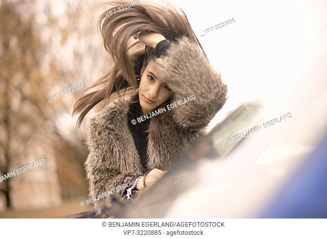 portrait of woman shaking hairs, leaning on car window in city, Munich, Germany