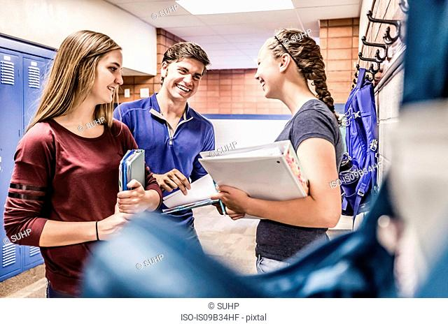 Teenage girls and boy holding notebooks and chatting in high school locker room
